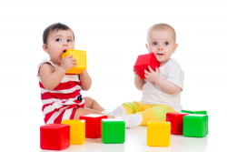 two infants playing together with soft building blocks